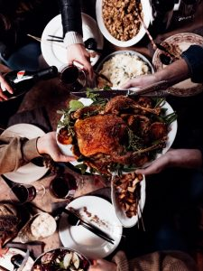 People passing a roast turkey across a table